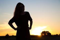 Silueta del adolescente en luz de la puesta del sol Foto de archivo libre de regalías