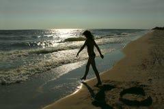 Silueta del adolescente en una playa vacía Foto de archivo