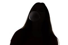 Silueta del adolescente que infla la burbuja Fotografía de archivo