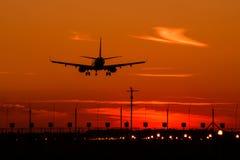 Silueta del aeroplano de Airbus A320 en la puesta del sol, acercamiento final Fotografía de archivo libre de regalías
