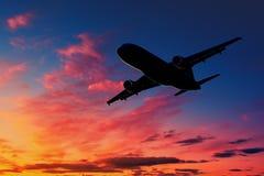 Silueta del aeroplano en el cielo en la puesta del sol foto de archivo