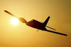 Silueta del aeroplano en la puesta del sol Fotografía de archivo