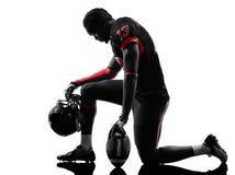 Silueta del arrodillamiento del jugador de fútbol americano imagen de archivo libre de regalías