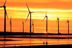 Silueta del arsenal de turbina de viento bajo puesta del sol Imagen de archivo