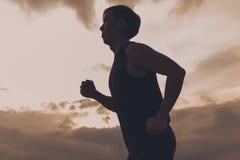 Silueta del atleta del corredor que corre en parque público concepto de la salud del entrenamiento de la salida del sol de la apt Fotografía de archivo