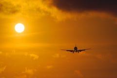 Silueta del avión grande en un fondo de la puesta del sol imagenes de archivo