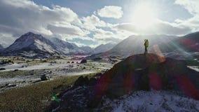 Silueta del backpacker que camina hacia el borde de un pico rocoso para comtemplar el panorama hermoso almacen de video