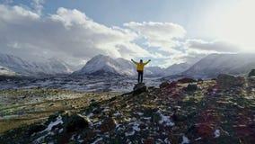 Silueta del backpacker que camina hacia el borde de un pico rocoso para comtemplar el panorama hermoso almacen de metraje de vídeo