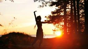 Silueta del baile de la mujer joven en puesta del sol