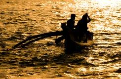 Silueta del barco con dos pescadores Imagen de archivo