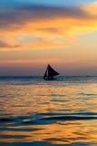 Silueta del barco de navegación en la puesta del sol Foto de archivo libre de regalías