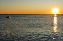 Silueta del barco de pesca en la salida del sol Imagen de archivo libre de regalías