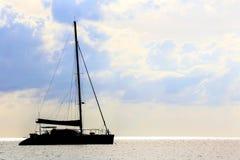 Silueta del barco de vela en un mar en la puesta del sol Imagenes de archivo