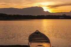 Silueta del barco en el lago en la puesta del sol Foto de archivo libre de regalías