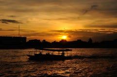 Silueta del barco en la puesta del sol en Chao Praya River Bangkok, T Foto de archivo