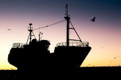 Silueta del barco pesquero en la puesta del sol Imagen de archivo