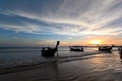 Silueta del barco y de la gente contra el cielo de la puesta del sol Fotos de archivo