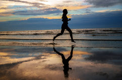 Silueta del basculador de la mujer que corre en la playa de la puesta del sol con la reflexión foto de archivo libre de regalías
