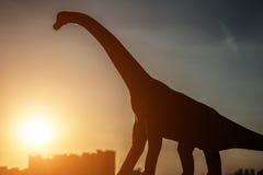 Silueta del brachiosaurus y de edificios en un rato de la puesta del sol Fotos de archivo libres de regalías