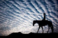 Silueta del caballo de montar a caballo del vaquero Foto de archivo