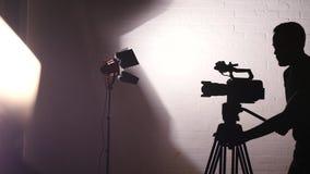 Silueta del cameraman Working Behind las escenas en estudio cinematográfico almacen de video