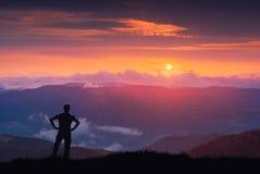 Silueta del caminante en una colina contra puesta del sol majestuosa colorida Fotografía de archivo libre de regalías