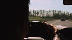 Silueta del coche de la impulsión del hombre en la autopista Tatuaje en las manos Día asoleado del verano traveling almacen de video