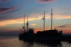 Silueta del ` de dos naves en el puerto en puesta del sol imagenes de archivo