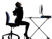 Silueta del dolor del dolor de espalda de la mujer de negocios que se sienta Foto de archivo libre de regalías