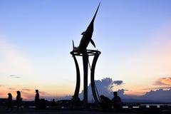 Silueta del embarcadero de la estatua de los peces espadas en la puesta del sol fotos de archivo libres de regalías