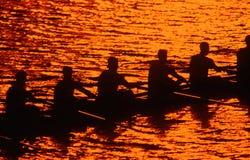 Silueta del equipo del rowing en la puesta del sol Fotos de archivo libres de regalías