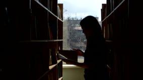 Silueta del estudiante joven que lee un libro en a metrajes