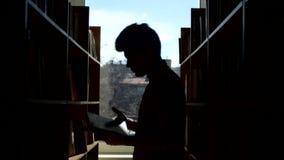 Silueta del estudiante joven que lee un libro en a almacen de metraje de vídeo