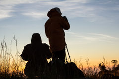 Silueta del fotógrafo en al aire libre con puesta del sol Imagen de archivo libre de regalías