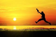 Silueta del fotógrafo que salta con la puesta del sol, paisaje marino Imagenes de archivo