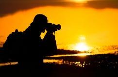 Silueta del fotógrafo en la puesta del sol Fotografía de archivo libre de regalías