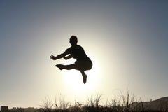 Silueta del gimnasta adolescente acrobático que salta con el sol detrás Imagen de archivo libre de regalías
