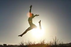 Silueta del gimnasta adolescente acrobático que salta con el sol detrás Foto de archivo