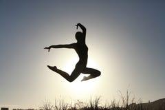 Silueta del gimnasta adolescente acrobático que salta con el sol detrás Fotos de archivo libres de regalías