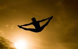 Silueta del gimnasta en cielo de oro Foto de archivo libre de regalías