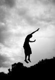 Silueta del gimnasta en el trampolín en cielo Imagen de archivo libre de regalías