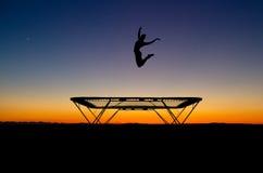 Silueta del gimnasta en el trampolín en puesta del sol Fotografía de archivo libre de regalías