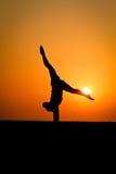 Silueta del gimnasta en la playa Imagen de archivo
