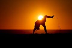 Silueta del gimnasta en la playa en la puesta del sol Fotografía de archivo