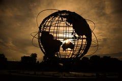 Silueta del globo del mundo en la puesta del sol imagen de archivo libre de regalías
