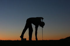 Silueta del golfista en la puesta del sol Imágenes de archivo libres de regalías