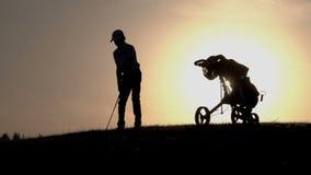 Silueta del golfista del muchacho con la bolsa de golf en la puesta del sol almacen de metraje de vídeo
