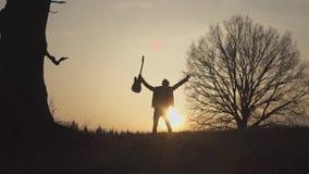 Silueta del guitarrista en la cámara lenta de la puesta del sol El guitarrista agita su mano almacen de metraje de vídeo