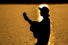 Silueta del guitarrista que toca una guitarra en el río debajo de imagen de archivo