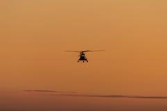 Silueta del helicóptero con el cielo de la puesta del sol imagenes de archivo